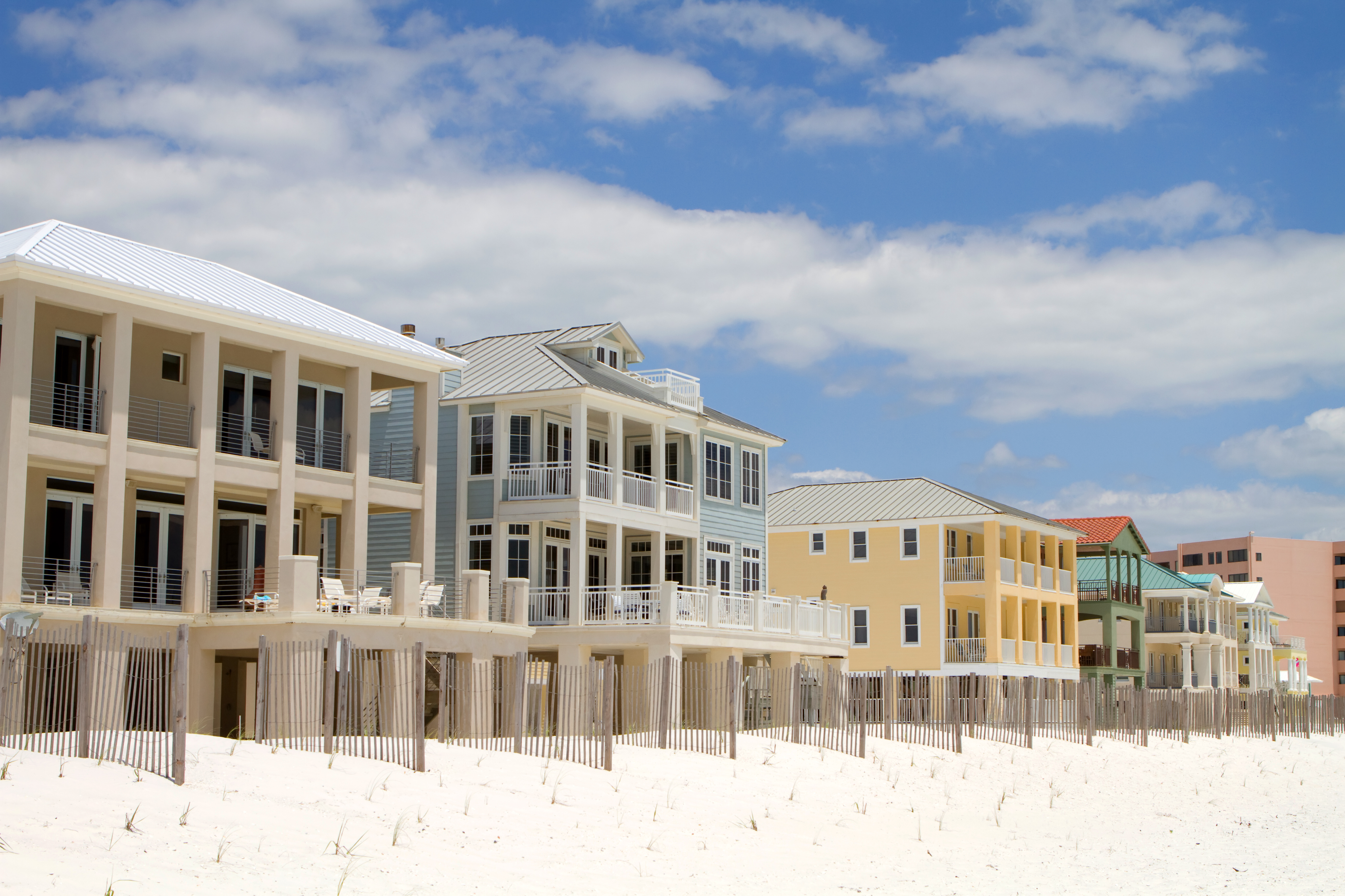 Expensive high end vacation beach homes and rentals built behind a small dune line and sand fences along the shoreline in Destin, Florida.